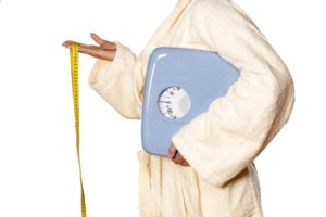 woman in bathrobe holding scales and a measuring tape